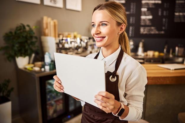 Glücklicher kaffeehauskellner in schürzen, der weißes papier in der hand hält