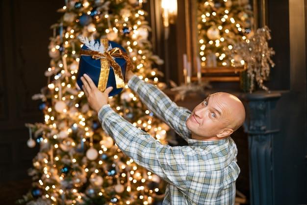 Glücklicher kahlköpfiger mann in einem hemd, das eine blaue schachtel mit einem geschenk auf dem hintergrund eines weihnachtsbaumes hält