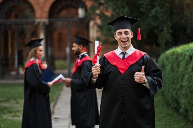 Glücklicher kaukasischer absolvent mit seinen klassenkameraden im abschlusskleid hält ein diplom auf dem campus.