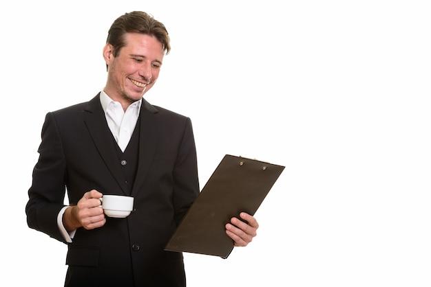 Glücklicher kaukasischer geschäftsmann, der zwischenablage liest, während kaffee hält
