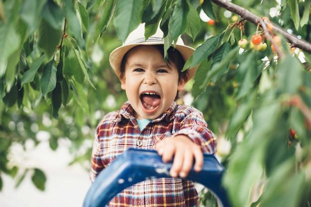 Glücklicher kaukasischer junge, der einen cowboyhut trägt, der an der kamera lächelt, während kirschen im baum essen