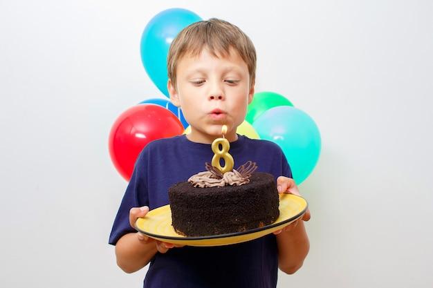 Glücklicher kaukasischer junge, der einen schokoladenkuchen mit kerze in seinen händen hält