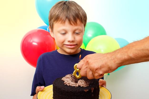 Glücklicher kaukasischer junge feiert geburtstag, indem er einen schokoladenkuchen hält