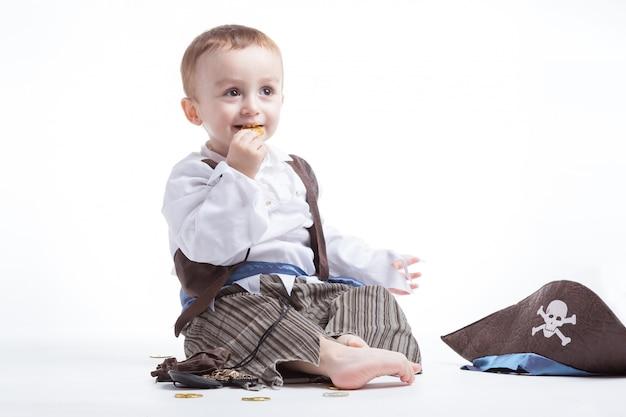 Glücklicher kaukasischer kleiner junge, als pirat verkleidet, der mit münzen und konfetti spielt. kleiner junge und kostümkonzept.