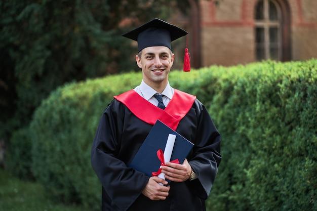 Glücklicher kaukasischer männlicher absolvent im abschlussglühen mit diplom, das die kamera auf dem campus betrachtet.