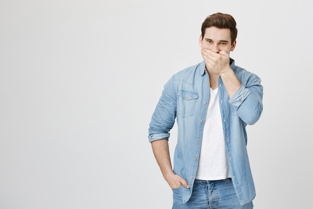 Glücklicher kaukasischer mann, der lacht, mund bedeckt, während kichert
