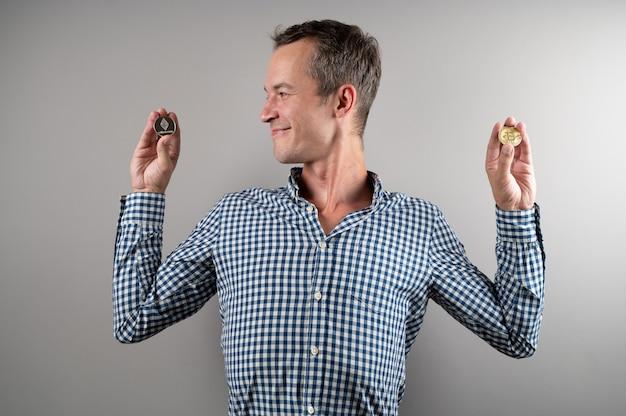 Glücklicher kaukasischer mann, der virtuelle währung-ethereum-münze und -bitcoin hält und über grauem hintergrund lächelt.