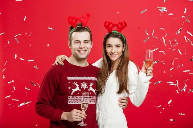 Glücklicher kaukasischer mann und frau in den renhüten das weihnachten feiern, das mit den sektkelchen, beglückwünschend auf weihnachten röstet.