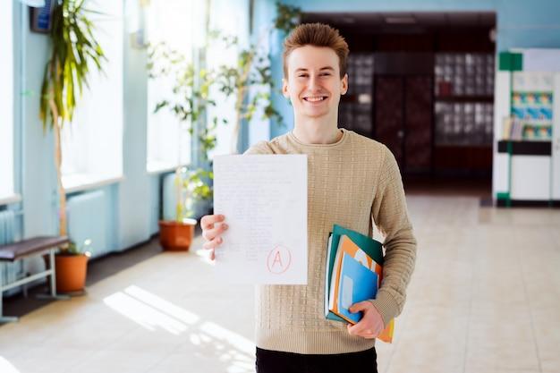 Glücklicher kaukasischer student hält überprüftes papier mit endprüfung mit grad a