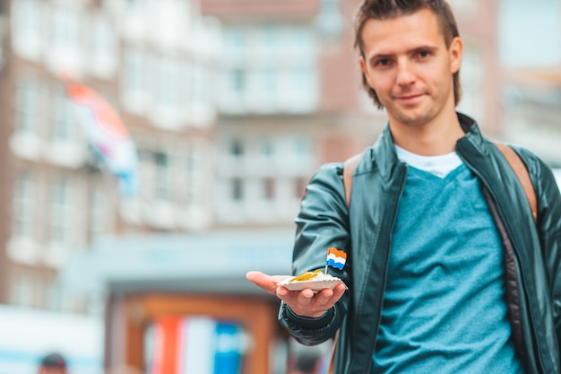Glücklicher kaukasischer tourist mit frischem hering mit zwiebeln und niederländischer flagge im traditionellen amsterdamer d...