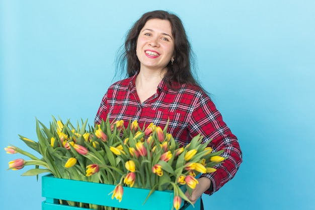 Glücklicher kaukasischer weiblicher florist, der große schachtel tulpen auf blauem hintergrund lacht und hält