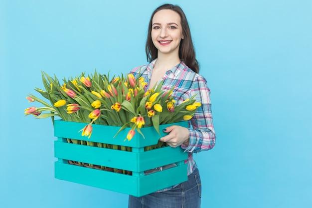 Glücklicher kaukasischer weiblicher florist, der lacht und große schachtel tulpen auf blauer oberfläche hält