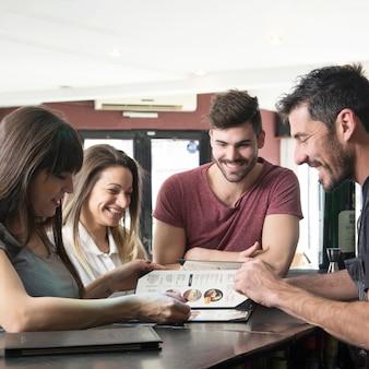 Glücklicher kellner und kunden, die menü in der bar betrachten