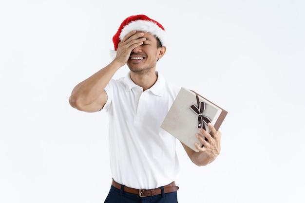 Glücklicher kerl, der versucht zu schätzen, was innerhalb der weihnachtsgeschenkbox ist