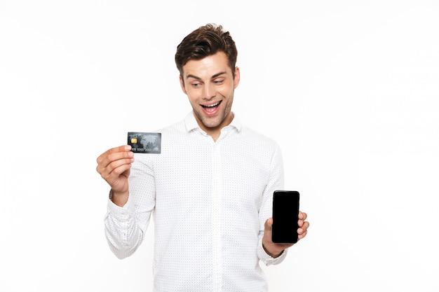 Glücklicher kerl mit dunklem haar, das handy und kreditkarte hält