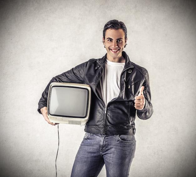 Glücklicher kerl mit einem alten fernseher