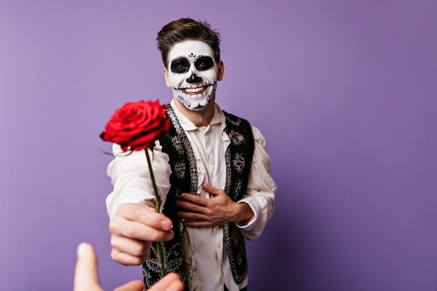 Glücklicher kerl mit freudigem blick ist dankbar und gibt seiner geliebten person rose. innenporträt des mannes mit halloween-make-up.