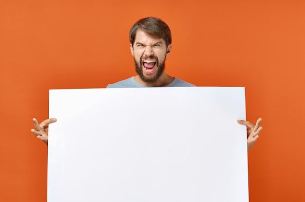 Glücklicher kerl mit modell in hand poster orange hintergrund kopieren raum.