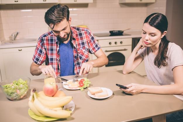 Glücklicher kerl sitzt und tisch und isst omelett. er schneidet essen mit messer und gabel in stücke. mädchen betrachtet telefon, das sie in den händen hält. sie ist gelangweilt und müde.