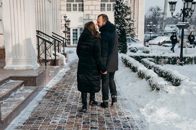 Glücklicher kerl und mädchen gehen durch die schneebedeckte stadt und lächeln sich zärtlich an. hochwertiges foto