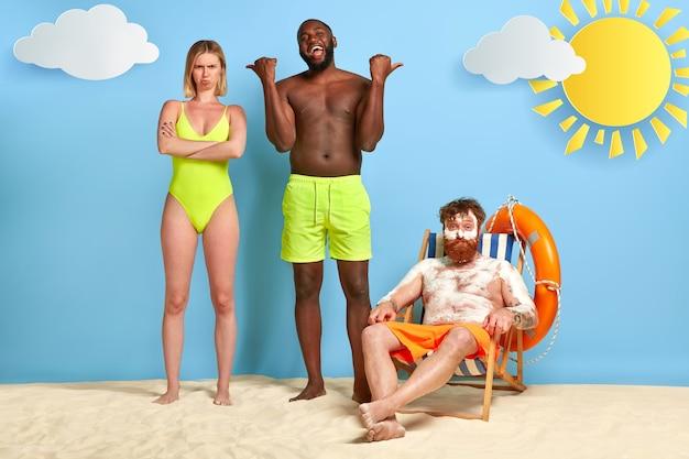 Glücklicher kerl zeigt auf rotschopf, der am strand mit sonnencreme aufwirft