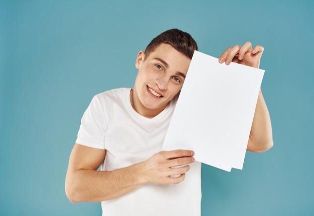 Glücklicher kerl zeigt einen flyer in seiner hand auf einem blauen hintergrundwerbemodell