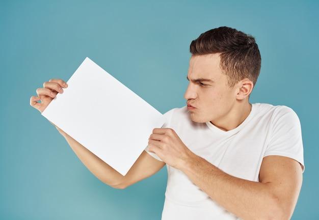 Glücklicher kerl zeigt einen flyer in seiner hand auf einem blauen werbemodell