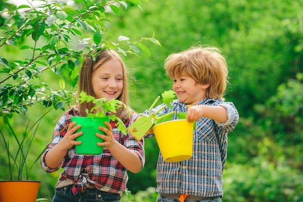 Glücklicher kinderbauer auf dem bauernhof mit landschaftshintergrund süßer kleiner junge und mädchen bewässerungsplan...