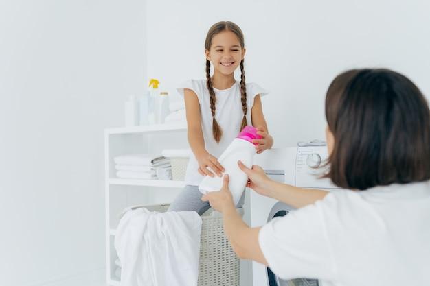 Glücklicher kinderhelfer und mutter haben spaß in der waschküche, waschen zusammen und lächelndes mädchen mit zwei zöpfen gibt der mama reinigungsmittel, steht im korb nahe waschmaschine. hausarbeit-konzept