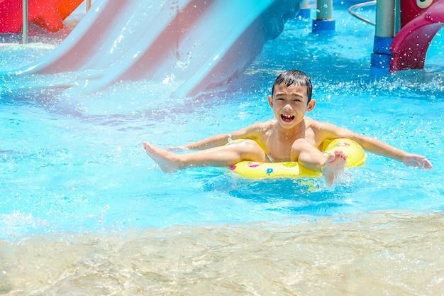 Glücklicher kinderjunge auf sicherheitsring im swimmingpool