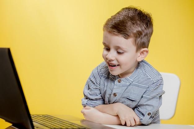 Glücklicher kinderjunge, der am tisch mit laptop sitzt und sich zur schule vorbereitet