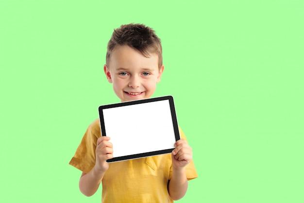 Glücklicher kinderjunge, der eine tablette für ihre informationen an der grünen wand hält