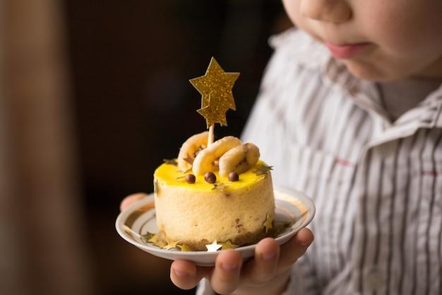 Glücklicher kinderjunge, der einen kuchen hält.
