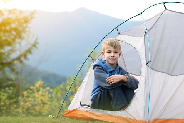 Glücklicher kinderjunge, der in einem touristenzelt am bergcampingplatz ruht und blick auf schöne sommernatur genießt. wandern und aktives lebensstilkonzept.