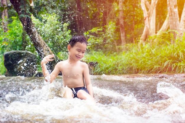 Glücklicher kinderjunge, der unter grüner regenschirmnatur spielt und sich versteckt