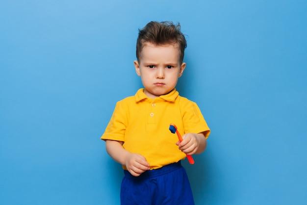 Glücklicher kinderjunge, der zähne mit zahnbürste auf blauem hintergrund putzt. gesundheitsversorgung, zahnhygiene. attrappe, lehrmodell, simulation