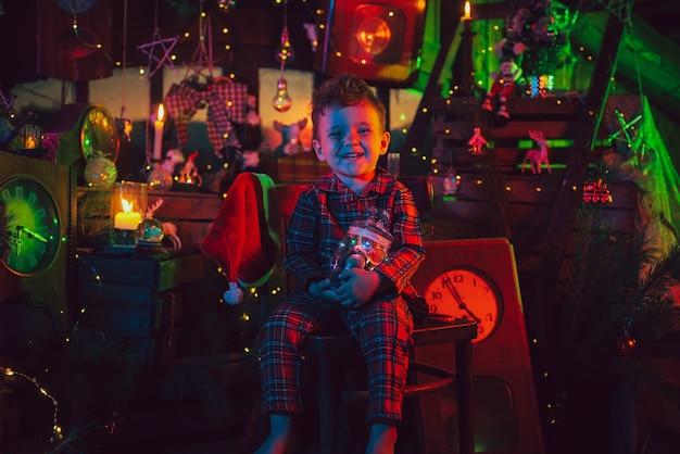 Glücklicher kinderjunge im weihnachtspyjama und einem hut, der helfer des weihnachtsmannes in der weihnachtszauberdekoration.