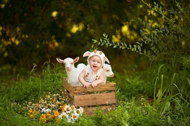 Glücklicher kinderjunge mit weißen ziegen im frühjahr auf natur im dorf mit grün und blumen.