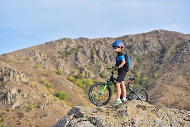 Glücklicher kinderjunge von 7 jahren, der spaß im herbstpark mit einem fahrrad am schönen herbsttag hat. aktives kind mit fahrradhelm