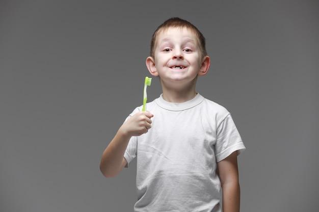 Glücklicher kinderkindjunge mit elektrischer zahnbürste auf grauem hintergrund. gesundheitswesen, zahnhygiene. modell, speicherplatz kopieren.