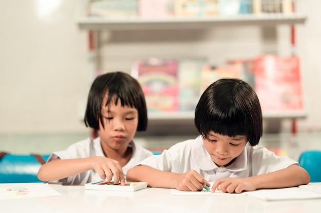 Glücklicher kinderstudent, der im klassenzimmer spielt und lernt.