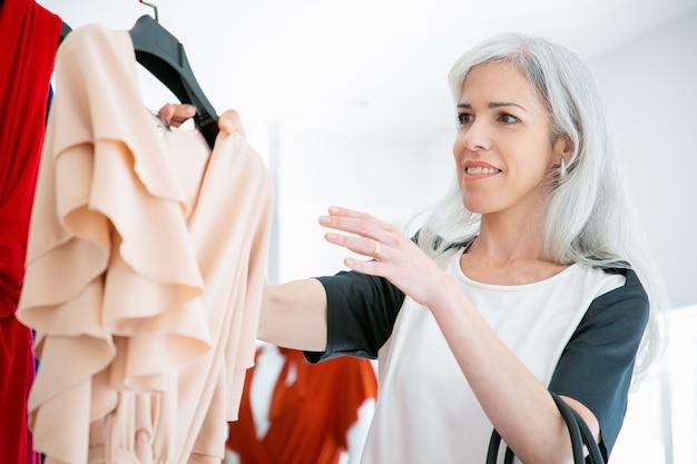 Glücklicher kleidergeschäftkunde, der kleiderbügel mit kleid vom gestell für versuch nimmt. frau, die kleidung im modegeschäft wählt. konsum- oder einzelhandelskonzept