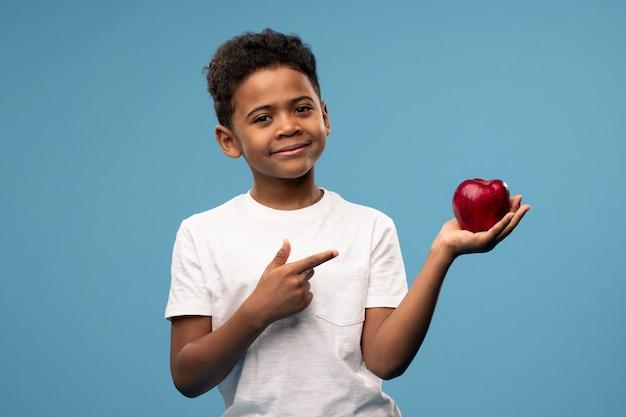 Glücklicher kleiner afrikanischer junge mit dem großen roten reifen apfel in der hand, der auf die frucht zeigt, die es als gesundes essen empfiehlt