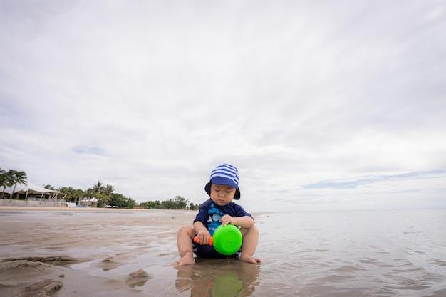 Glücklicher kleiner asiatischer junge im badeanzug, der auf strand spielt. sonnenuntergang