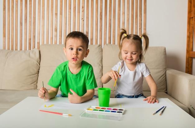 Glücklicher kleiner bruder und schwester, die mit pinsel und farbe auf papier am tisch im raum zeichnen
