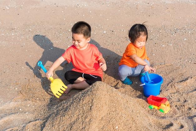 Glücklicher kleiner fröhlicher bruder und schwester zwei kinder lustiges graben spielen spielzeug mit sand am strand