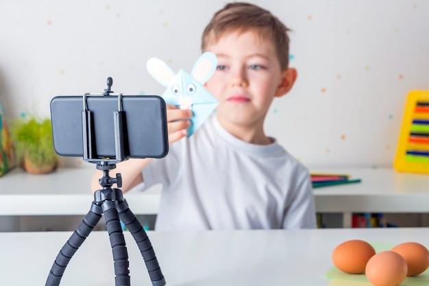 Glücklicher kleiner junge blogger, der live-video-streaming auf smartphone aufzeichnet. der vorschulkind führt die online-meisterklasse für osterhandwerker zu seinen anhängern. blogging-konzept, hintergrundbeleuchtung, selektiver fokus.