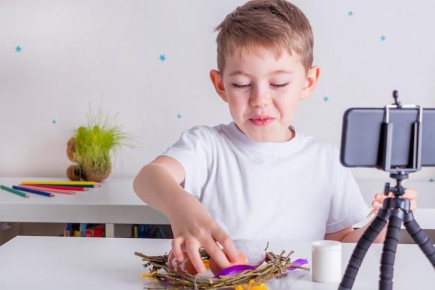 Glücklicher kleiner junge blogger, der live-video-streaming auf smartphone aufzeichnet. online-oster-meisterkurs zum malen von eiern an anhänger. blogging-konzept, hintergrundbeleuchtung, selektiver fokus.