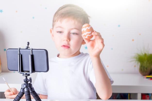 Glücklicher kleiner junge blogger, der live-video-streaming auf smartphone aufzeichnet
