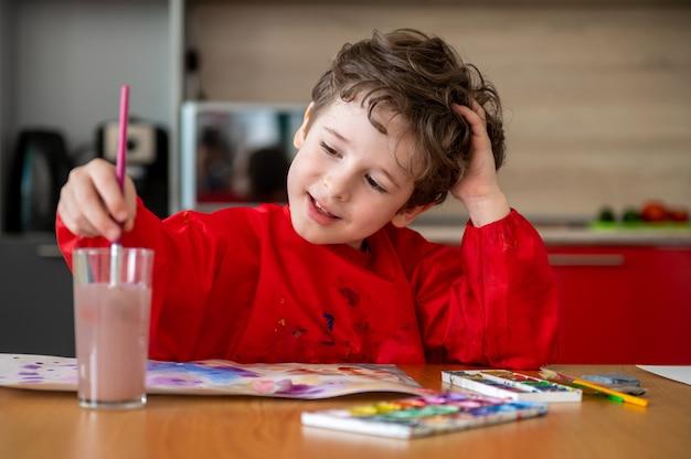 Glücklicher kleiner junge, der bilder zu hause zeichnet